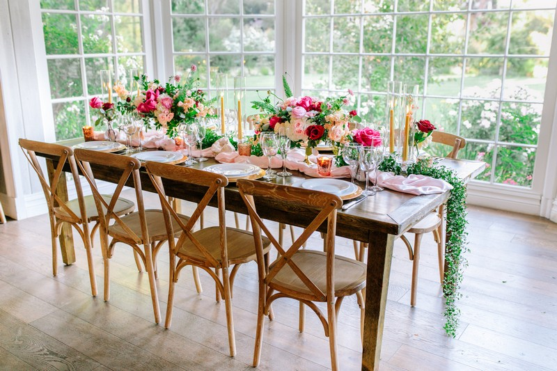 Wedding table styled with burgundy and pink flowers