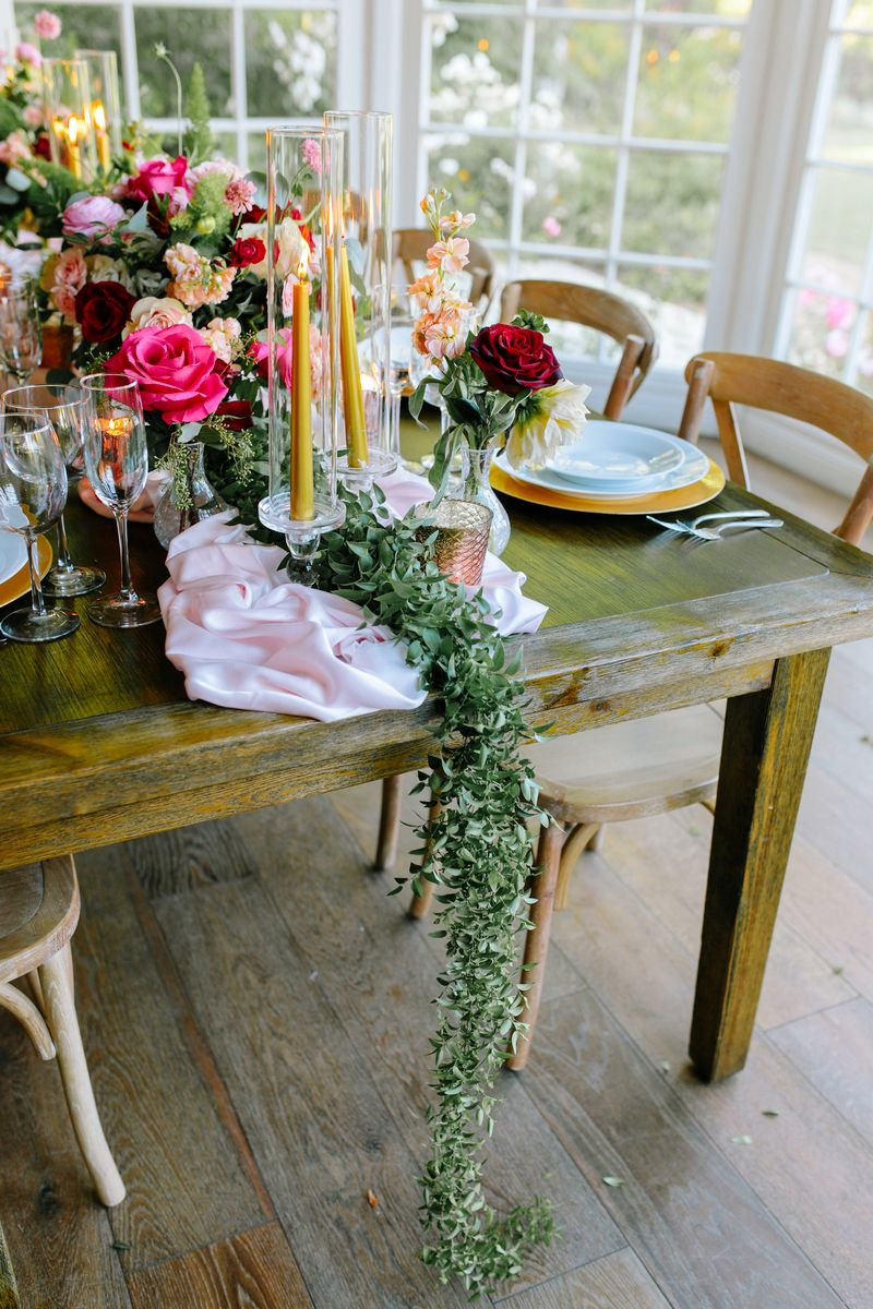 Green foliage runner hanging off wedding table