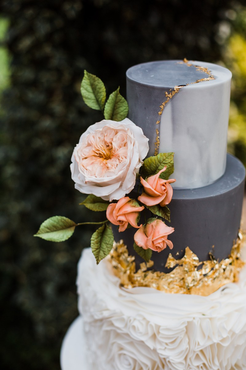 Coral flowers and gold leaf on wedding cake