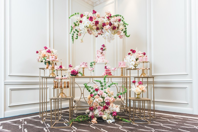 Elegant pink and gold dessert tables styled with flowers