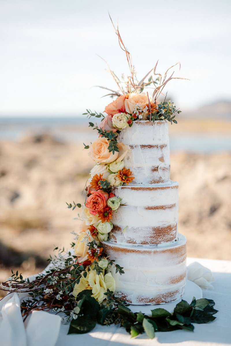 Naked wedding cake with cascading fresh flowers
