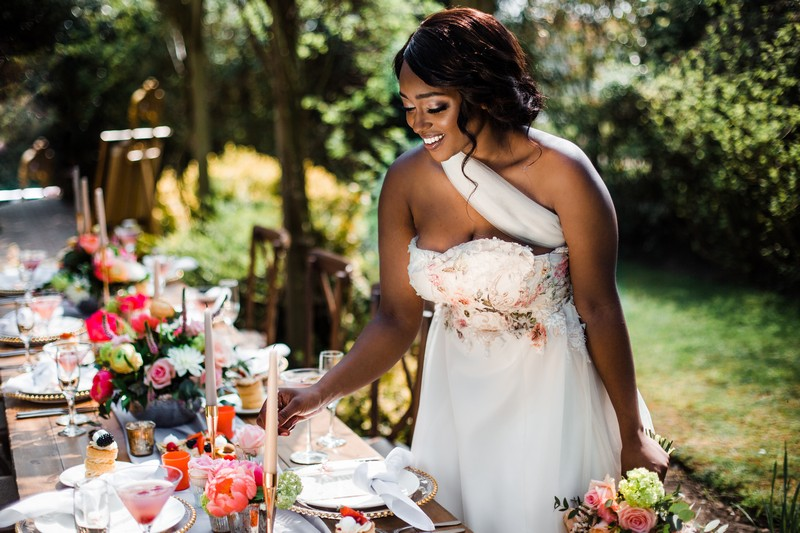 Bride smiling standing by wedding table