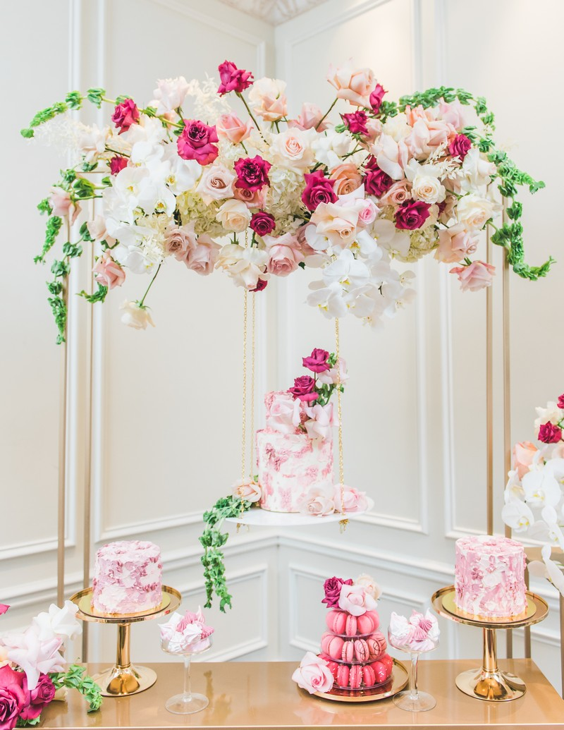 Desserts and cake on gold table with flowers overhead