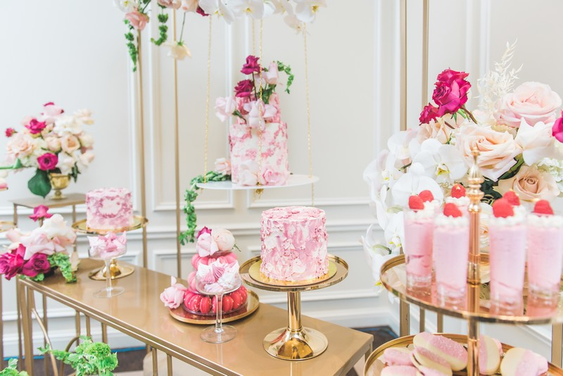 Gold table of pink wedding cakes and desserts