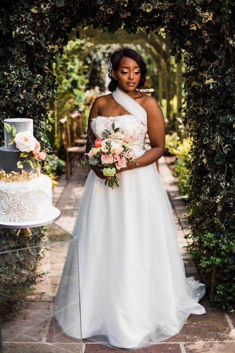 Bride standing holding bouquet next to wedding cake