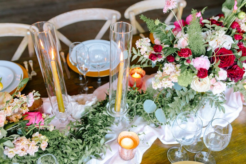 Tall candles in glass cylinders on wedding table
