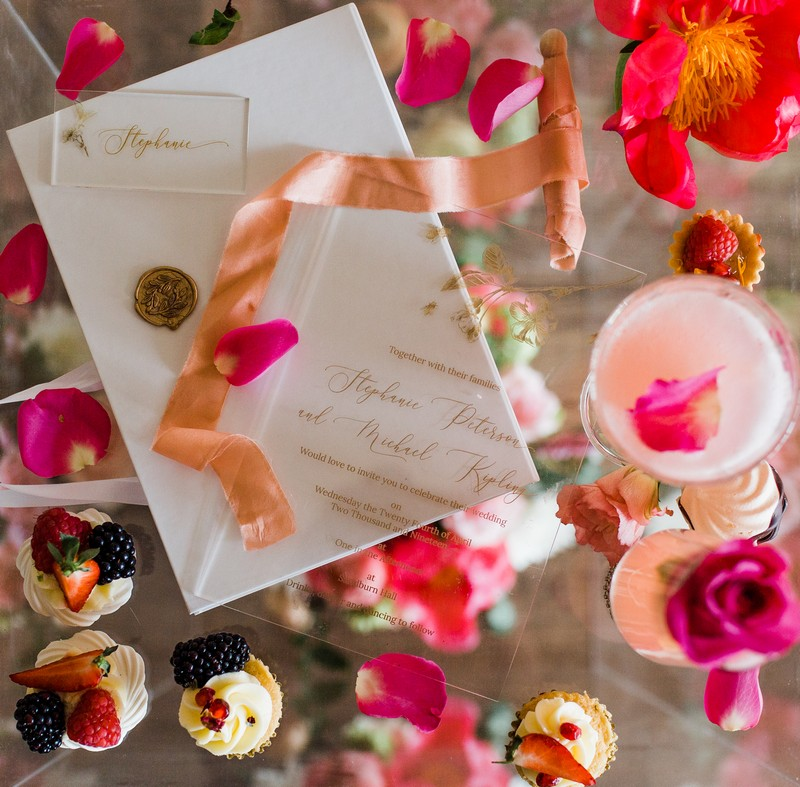 Coral and pink details with small wedding desserts and perspex stationery