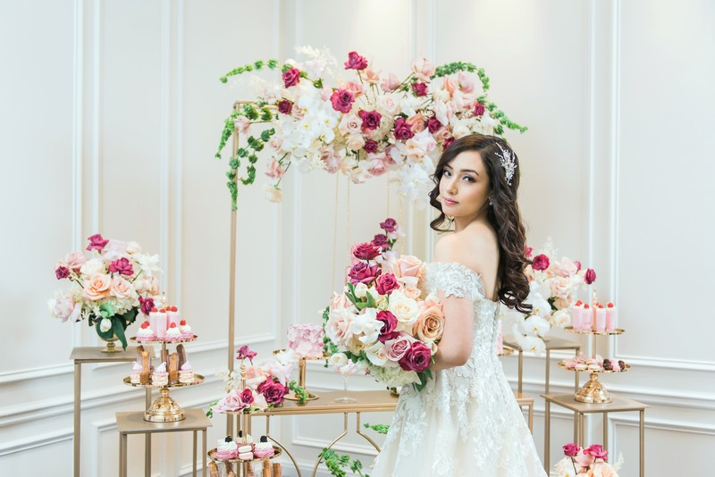 Bride holding pink bouquet in front of gold wedding dessert tables
