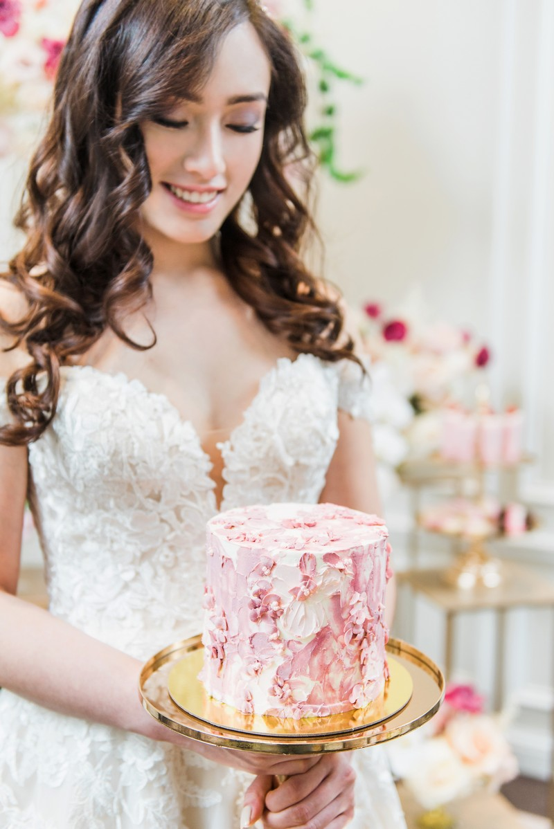 Bride holding pink wedding cake