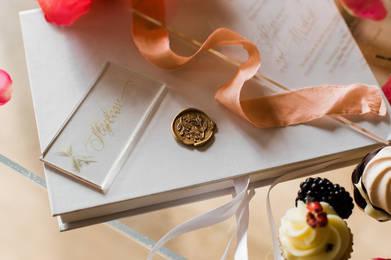 Gold wax seal with coral coloured ribbon