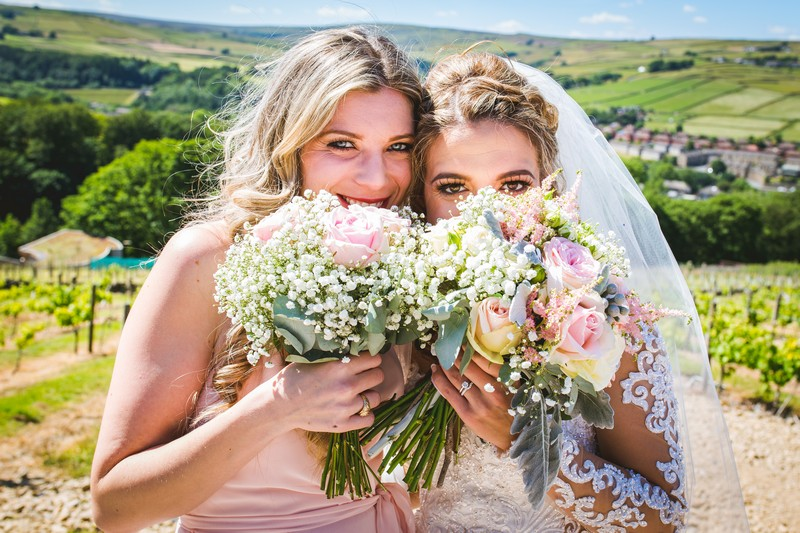 Bride and bridesmaid holding bouquets in front of faces