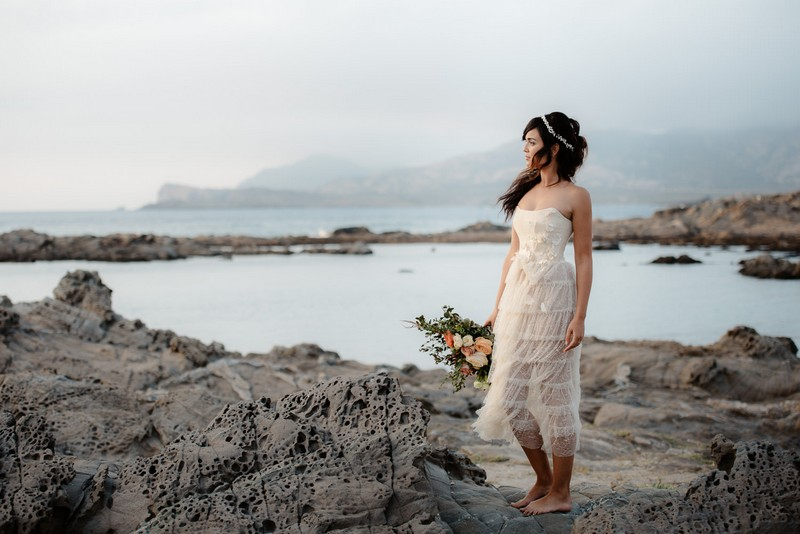 Boho bride holding bouquet looking out to sea