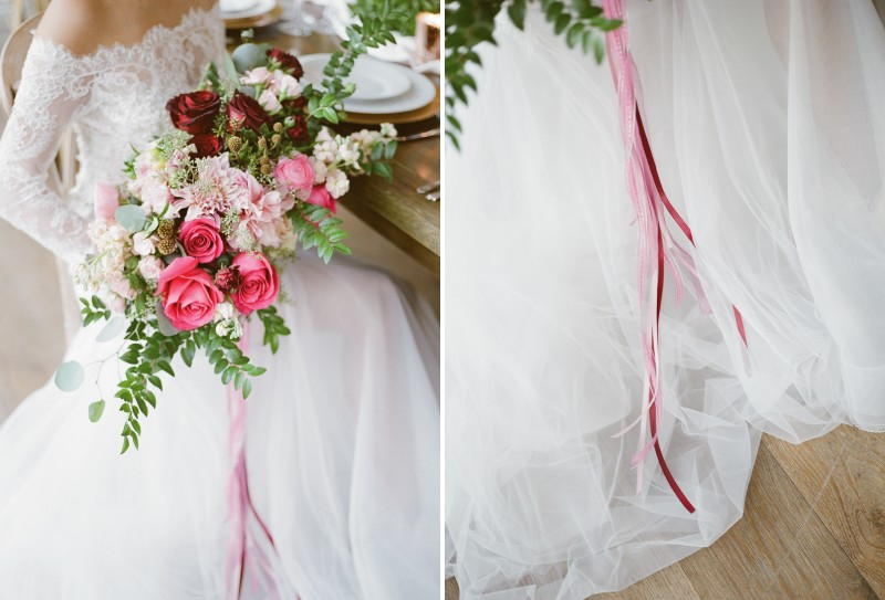 Burgundy and pink wedding bouquet with ribbon trailing down tulle skirt