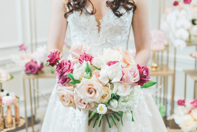 Bride holding bouquet of pink and cream flowers