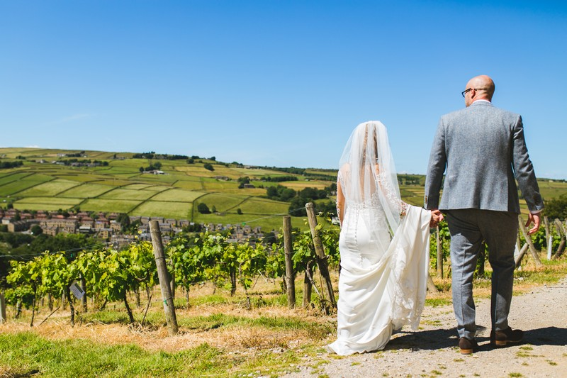 Bride and groom holding hands as they walk around Holmfirth Vineyard