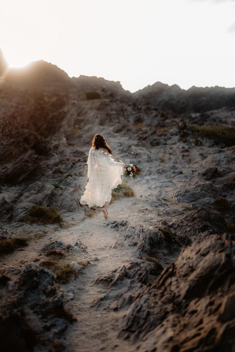 Bride walking up sandy hill on La Pelosa beach