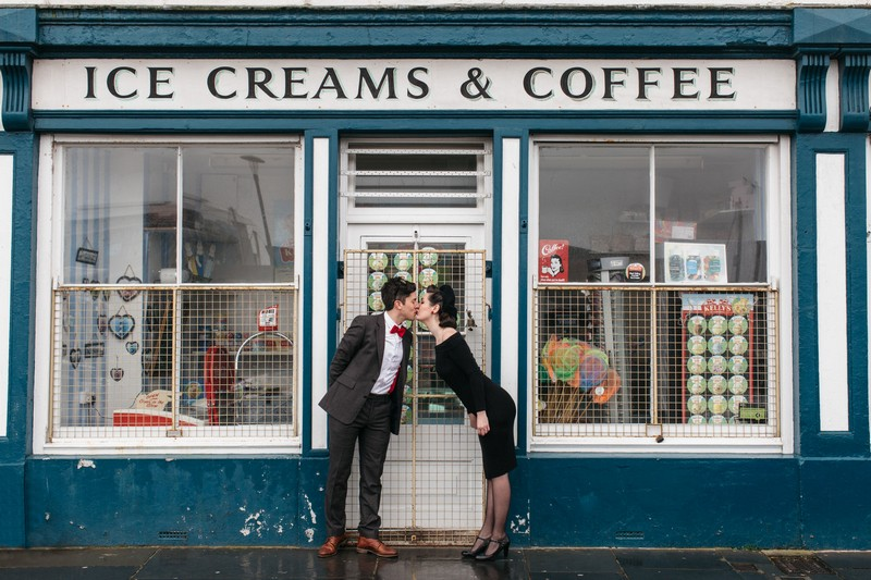 Couple leaning forward to kiss each other in front of ice creams and coffee shop - Picture by Emma Barrow Photography