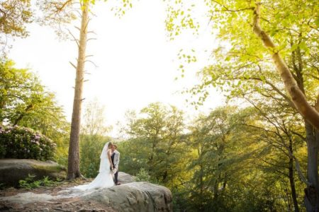 Bride and groom standing in woodland - Picture by Helen England Photography