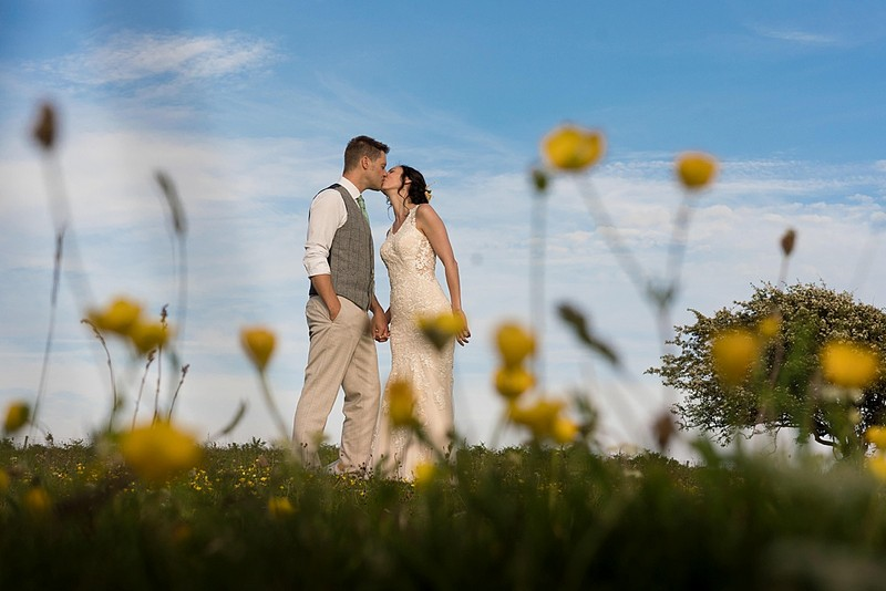 Bride and groom kissing behind yellow flowers - Picture by Linus Moran Photography