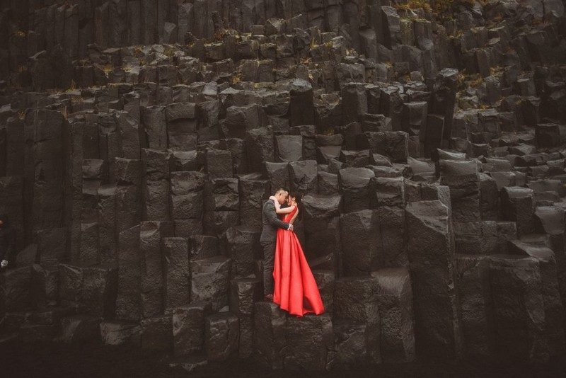 Bride and groom standing on edge of black rocks - Picture by Alexa Penberthy Photography