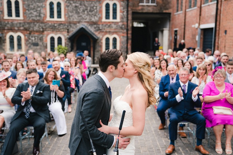 Bride and groom kissing at end of outdoor wedding ceremony - Picture by Married to my Camera