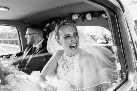 Happy bride with beaming smile in back of wedding car - Joss Denham Photography