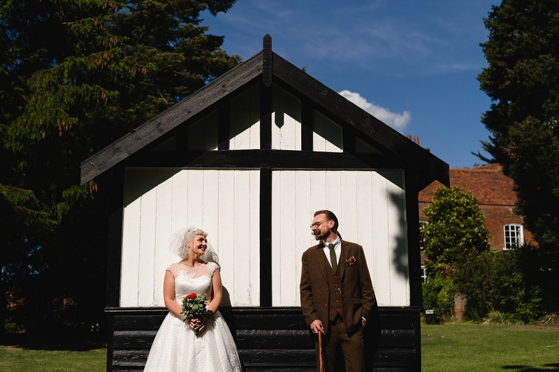 Vintage bride and groom standing up against white wooden building in garden - Picture by Sam Gibson Photography