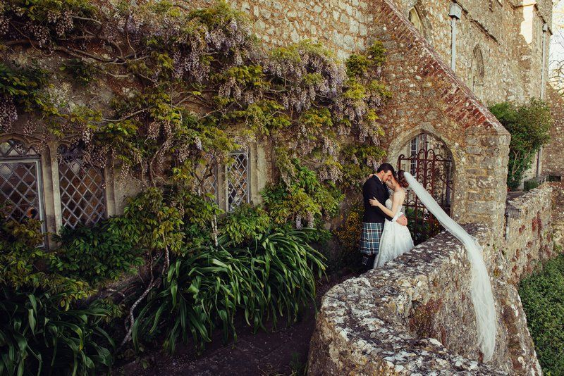 Bride and groom hugging outside venue with bride's veil hanging over wall - Picture by Emma-Jane Photography