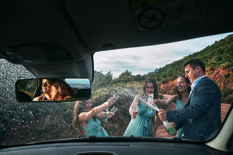 Man with bridesmaids spraying champagne with reflection of bride and groom in car mirror - Picture by Emin Kuliyev