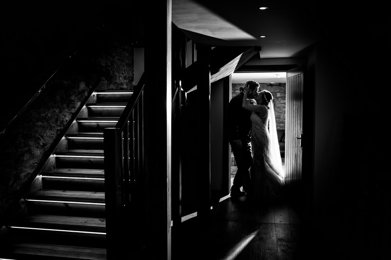 Bride and groom kissing in doorway next to stairs - Picture by Giles Atkinson Photography