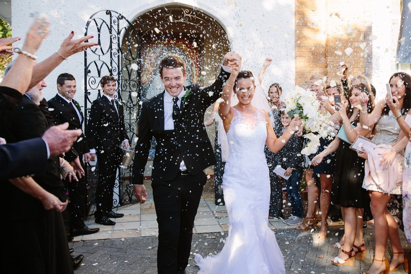 Bride and groom with arms in the air as they walk through confetti shower - Picture by Estefania Romero Photography