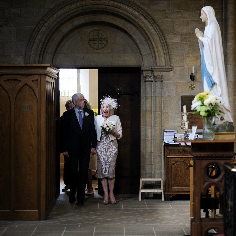 Excited lady walking into church for wedding ceremony - Picture by Simon Dewey Photography