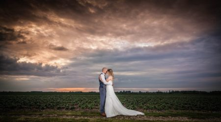 Bride and groom touching heads in a field with grey sky overhead - Picture by Peter Rollings Photography