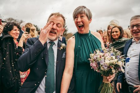 Excited bride with groom after walking through confetti shower - Picture by Tracey Warbey Photography