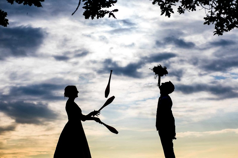 Silhouette of bride juggling clubs and groom balancing bouquet on his chin - Picture by Aaron Storry Photography