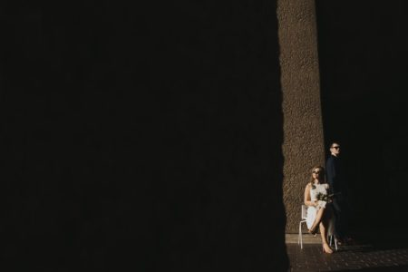 Bride sitting and groom standing in light of dark corridor - Picture by Joasis Photography