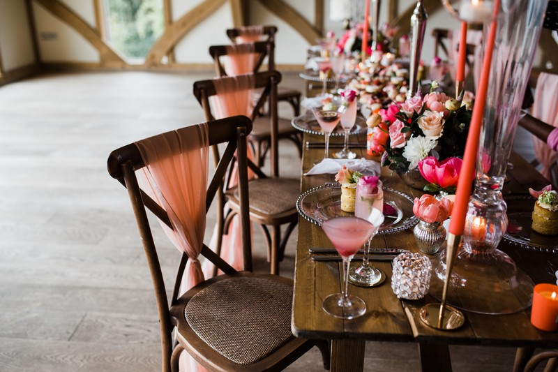 Wedding chairs with coral coloured sashes