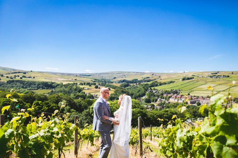 Bride and groom at Holmfirth Vineyard with Holme Valley hills in background