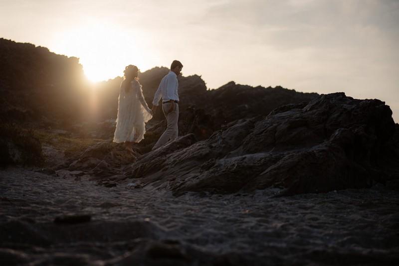 Couple walking across La Pelosa beach as sun goes down