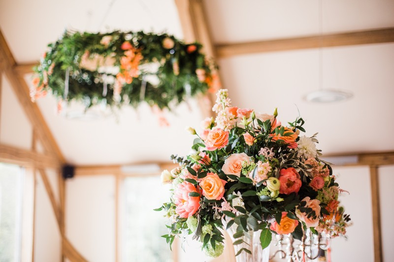 Coral coloured wedding table flowers