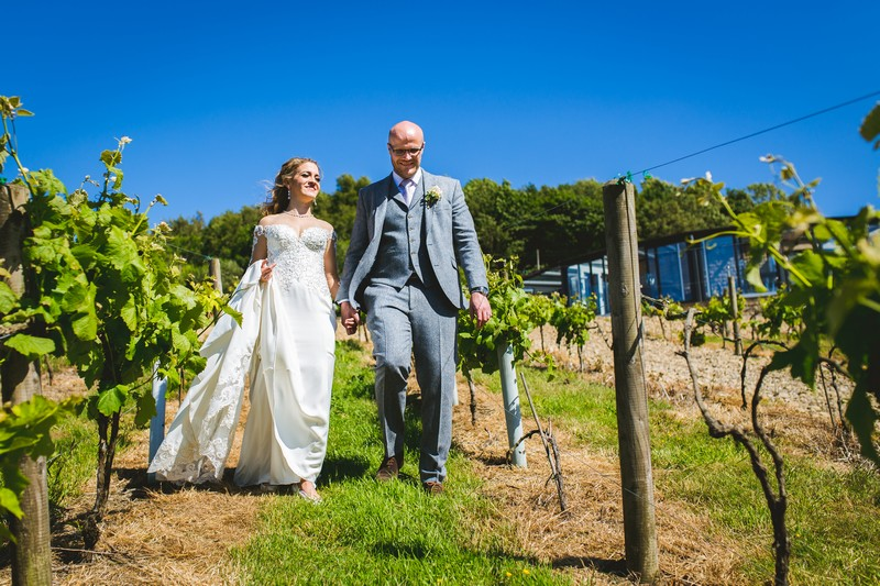 Bride and groom walking through Holmfirth Vineyard