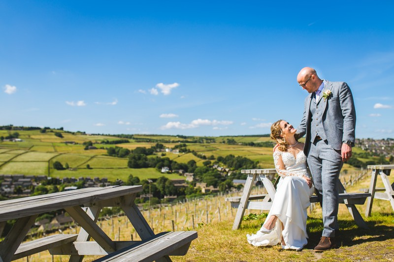 Bride and groom sitting on picnic bench at Holmfirth Vineyard