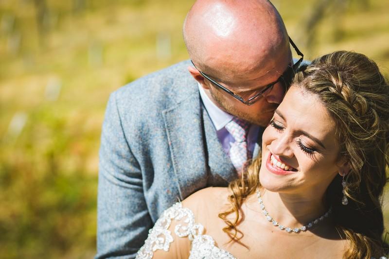 Groom kissing bride on side of her head