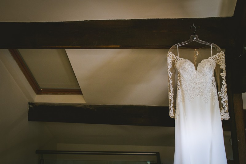 Wedding dress hanging from beam