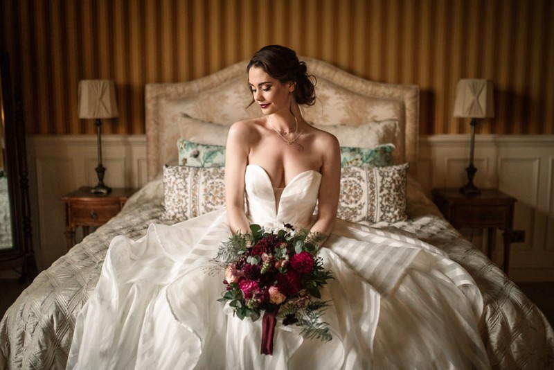 Bride sitting on bed holding bouquet
