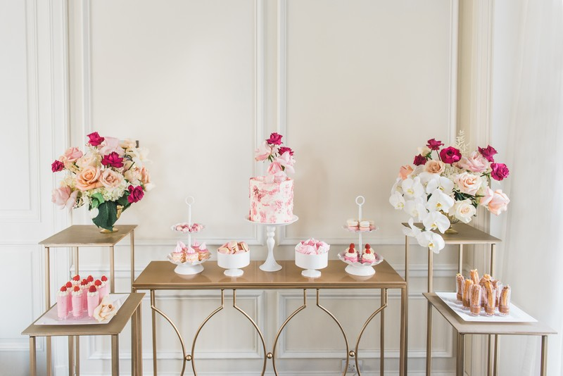 Gold dessert tables with pink flower displays