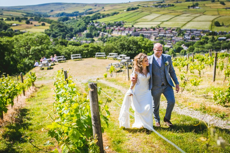 Bride and groom walking through Holmfirth Vineyard
