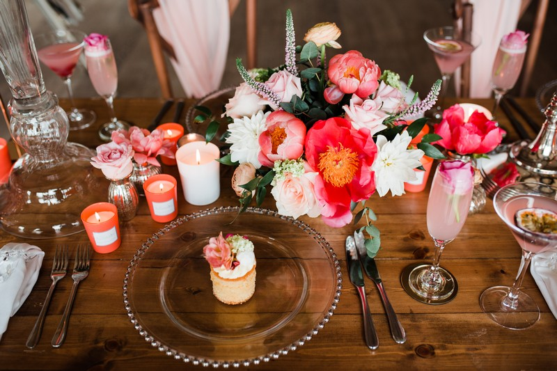 Small cake on clear plate and coral wedding table flowers and candles