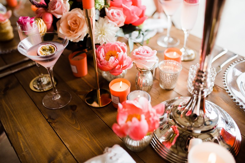 Living coral coloured table flowers and candles