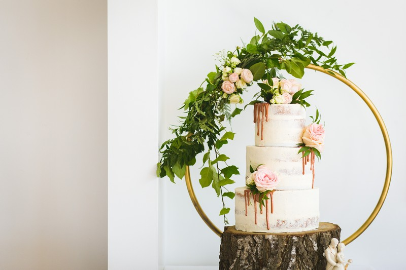 Semi naked wedding cake with flowers and drip icing